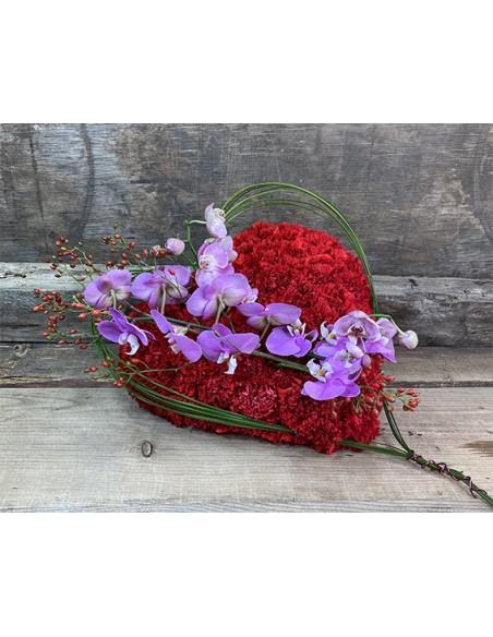 Composizione di fiori freschi a forma di cuore  realizzata con  garofani e orchidee phalaenopsis. Dimensioni: 32 x 34 cm.